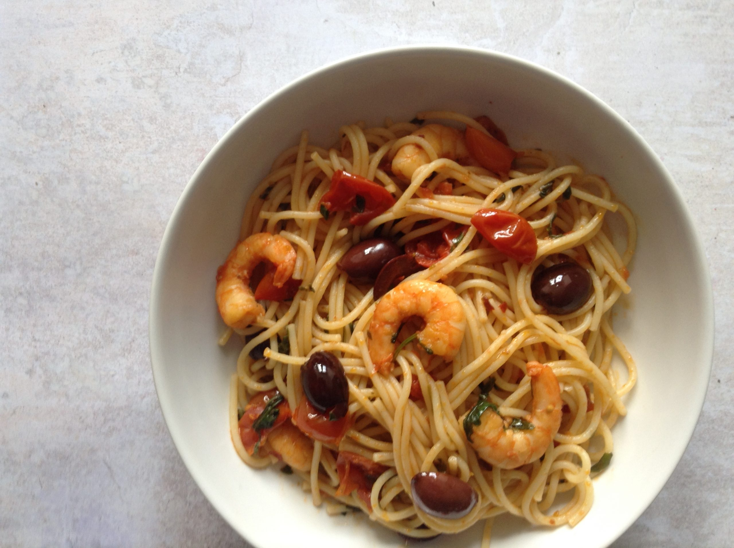 Spaghetti with black olives, king prawns and cherry tomatoes