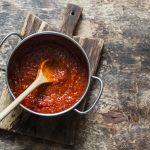 Classic homemade tomato sauce in the pan on a wooden chopping board, healthy Italian tomatoes sauce,
